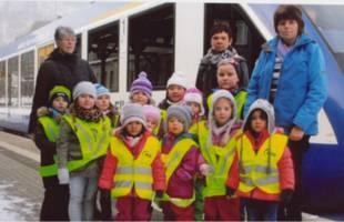 Die Kinder und Erzieher der Dachspatzengruppe der Kita Regenbogen vor einem Zug des Unternehmens HEX [(c): Herr Kalb, HEX]