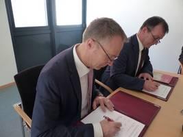 Halberstadts Oberbürgermeister Andreas Henke (links) und Ralf Quednau, Vorstand der Harz AG, unterzeichnen die Kooperationsvereinbarung zur Einführung des Harzer Urlaubs-Tickets in der Kreisstadt Halberstadt. [(c): Ute Huch]