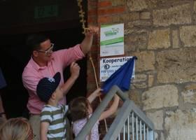 Martin Pasewalk, Leiter der Kita Holzbergwichtel, enthüllt gemeinsam mit den Kindern die neu angebrachte Tafel für die Kooperation zwischen dem FSV 1920 Sargstedt e.V. und der Kindertagesstätte. [(c): Kita Holzbergwichtel]
