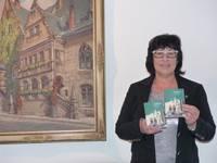 """Christiane Strohschneider, Leiterin der Halberstadt Information, präsentiert die neue Broschüre """"Stadtspaziergänge im Schatzjahr 2018""""."""