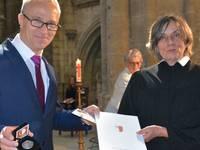 Oberbürgermeister Andreas Henke (Die Linke) überreicht Pfarrerin Hannah Becker die Verdienstmedaille der Stadt.