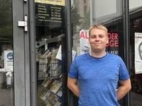 Archivmitarbeiter Robert Pilz vor dem Schild mit neuem Namen und neuen, ab 1.10. gültigen Öffnungszeiten am Domplatz 31