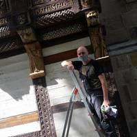 Museumsmitarbeiter André Pohl bei der Behandlung der Holzfiguren nach Wiederanbringung