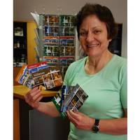 Petra Stange, Mitarbeiterin der Halberstadt Information, präsentiert die sechs neuen und farbenfrohen Halberstadt-Postkarten.