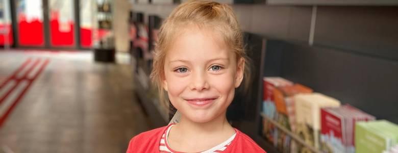 Die 6-Jährige Emilia schaut sich in der Tourist Information den Ferienkalender der Stadt Halberstadt an. [(c) Tourist Information Halberstadt]