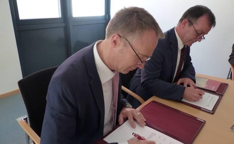 Halberstadts Oberbürgermeister Andreas Henke (links) und Ralf Quednau, Vorstand der Harz AG, unterzeichnen die Kooperationsvereinbarung zur Einführung des Harzer Urlaubs-Tickets in der Kreisstadt Halberstadt. [(c) Ute Huch]