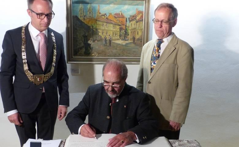 Friedrich Wilhelm Schröter (links) trägt sich auf den Wunsch des Oberbürgermeisters Andreas Henke und des Stadtratspräsidenten Dr. Volker Bürger (rechts) in das Goldene Buch der Stadt ein. [(c) Ute Huch]